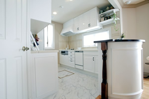 横長のI型キッチンに半円状のカウンターを組み合わせ。調理しやすく収納力もある