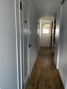 玄関から見た廊下。<br>白いドアは既存のものを白く塗装することで費用を抑えた
