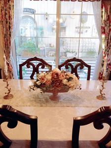 テーブルの上のフラワーアレンジメントは家を建ててからの趣味。奥に見える裏庭は数年かけてDIYをし、明るい空間となった