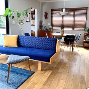 リビングダイニング。青色のデイベッドはデンマークを代表する家具デザイナー、ハンス・J・ウェグナーのGE258