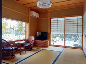 雪見障子から見る雪景色の庭。畳に座りながら眺める風景は格別