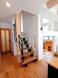 リビング階段は「ウッドワン」を使用。中2階に上がるまでの6段分はデザイン階段にしている。スキップ下の様子が見通せるよう、三連ガラスを入れた