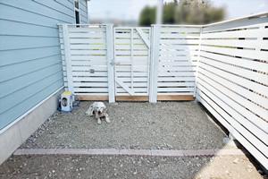 フェンスを作り、ノーリードでも走り回れるようにしたドッグラン。 白いフェンスは目隠しとしても活躍してくれている