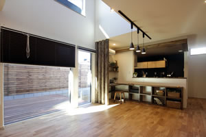吹き抜けのある21畳のリビング。将来的に15畳+6畳にも変更できる。床の高さとウッドデッキの高さを合わせ、空間の広がりを感じられるようにしている。床材はナラを使用