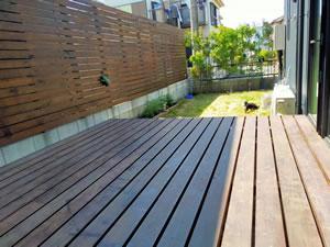 キャプション:庭にはウッドデッキを設置。外から見える部分は天然芝、室内からしか見えないところには人工芝と使い分けている