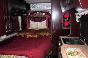 ベッド側、キャプション:常設のダブルベッドは約1900mm×1300mmの大きさ。特注の寝具カバーやカーテンなどでゴージャス感を演出